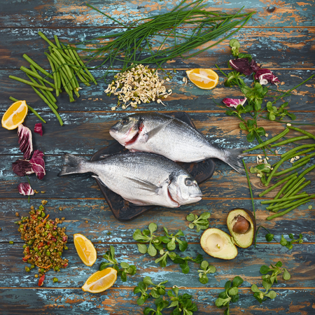 Dorado and natural raw ingredients for healthy food on rough dyed wooden background.