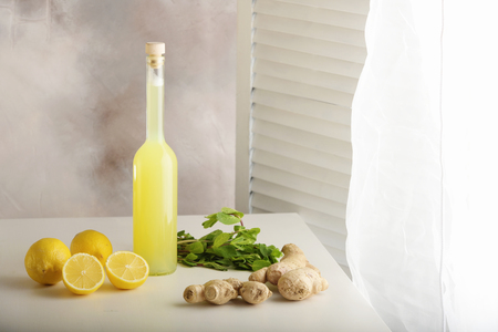 Bottle of homemade juice with ginger and lemon on light background. Horizontal Archivio Fotografico