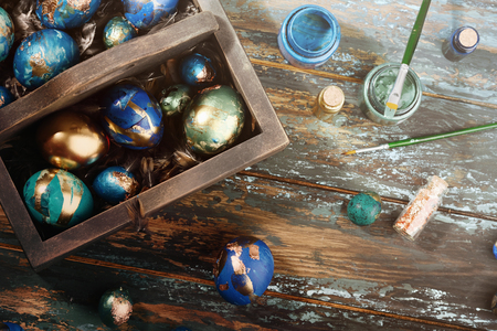 Painted colored Easter eggs in dark wooden box on dark wooden background. Boho stile.
