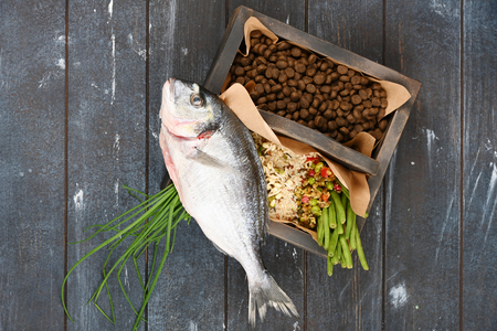 Special pet food VS natural pet food. Ingredients turkey, groats, rise, greens and sprouts in brown wooden box on rough dyed wooden background. Flat lay. Standard-Bild