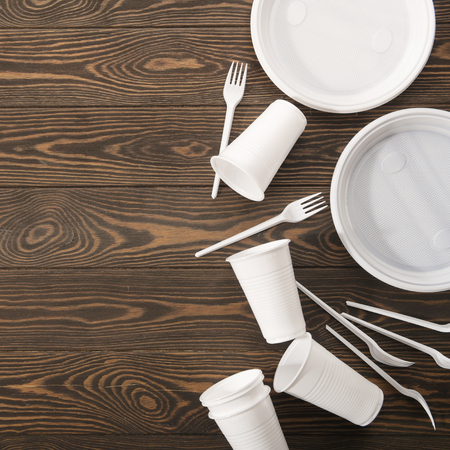 Plastic tableware on wooden background. Environmental protection. Secondary processing. The concept of zero waste.