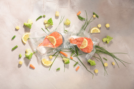 Sous Vide cooking concept. Vacuum packed ingredients arranged on light background. Top View.