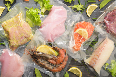 Sous Vide cooking concept. Vacuum packed ingredients arranged on wooden dyed background. Top View. 版權商用圖片
