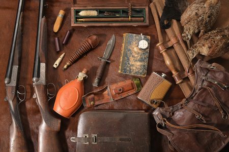 Hunting concept with woodcock, shotgun, knife and ammunition for hunting arranged on brown background. Wildfowl hunting.