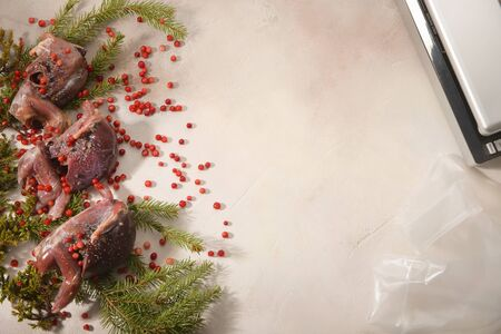 Ptarmigan, fir-tree branches and cowberry arranged on light background. Sous Vide cooking. Stock Photo