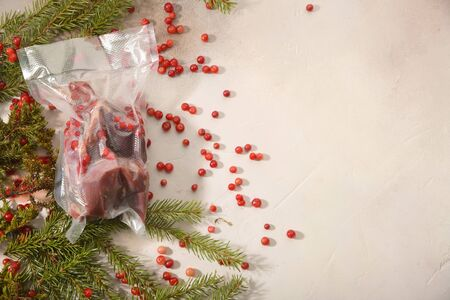 Ptarmigan, fir-tree branches and cowberry arranged on light background. Sous Vide cooking.