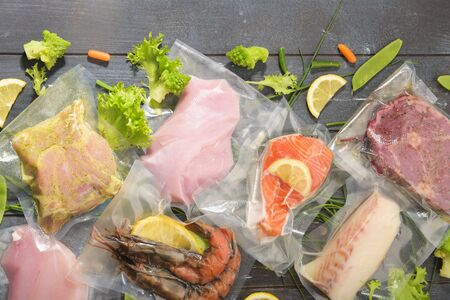 Sous Vide cooking concept. Vacuum packed ingredients arranged on wooden dyed background. Top View. Stock Photo