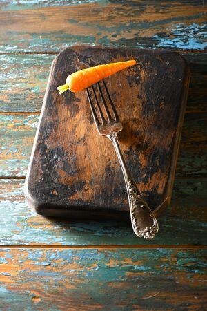Carrot on antique fork on burned-out kitchen board on rough dyed wooden blue table. Reklamní fotografie