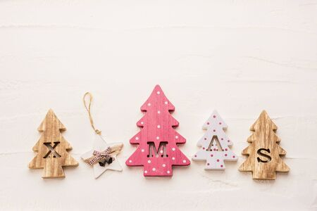 Four decorative wooden Christmas trees with carved letters xmas and christmas ornaments on a white textured background. Flat lay. Stock fotó