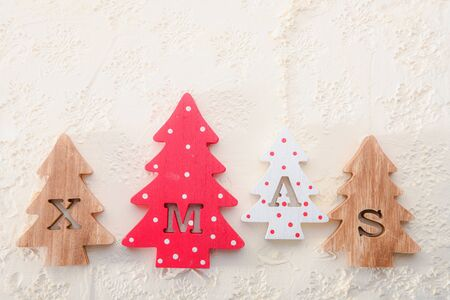 Four decorative wooden Christmas trees with carved letters xmas on a white textured background. Flat lay. Stock fotó