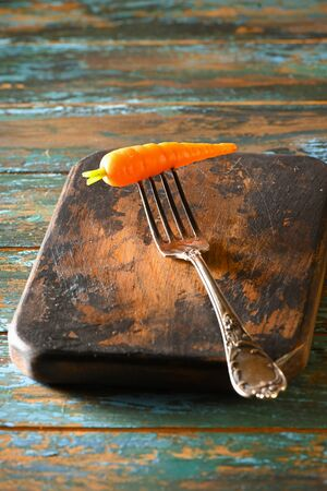 Carrot on antique fork on burned-out kitchen board on rough dyed wooden blue table. Stock fotó