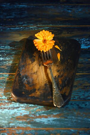 Marigold flower on antique fork on burned-out kitchen board on rough dyed wooden blue table.