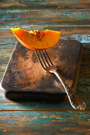 Pumpkin Slice on antique fork on burned-out kitchen board on rough dyed wooden blue table.