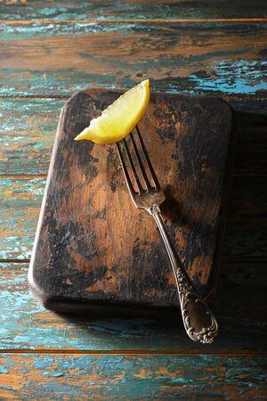 Slice lemon on antique fork on burned-out kitchen board on rough dyed wooden blue table.