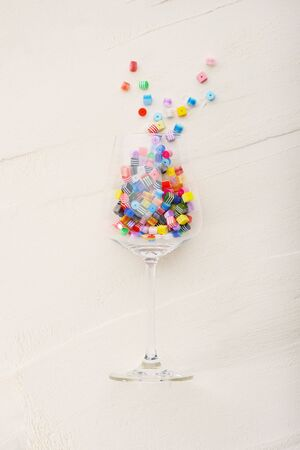 Multi-colored beads inside a wine glass on a white textured background. Flat lay.