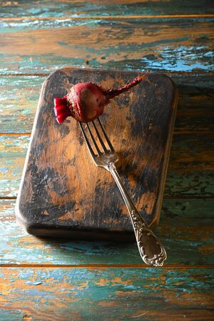 Beet on antique fork on burned-out kitchen board on rough dyed wooden blue table. Stock fotó