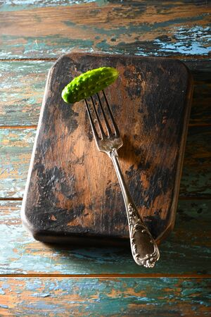 Cucumber on antique fork on burned-out kitchen board on rough dyed wooden blue table.
