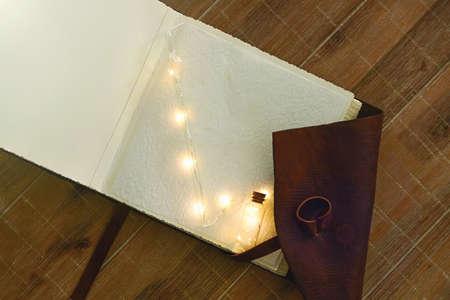 Open book with a miniature flashlight lies on a wooden table. Close-up. Standard-Bild