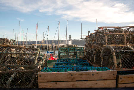 lobster pots: view of scarborough light house through stacked lobster pots