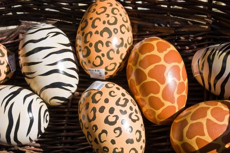 Colorful wooden eggs for sale in a basket. Stock Photo