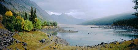 Panoramic landscape of misty lake with autumn foliage