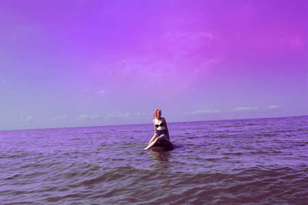 Red-haired girl sitting on a rock around the sea, lakes and oceans  Sky as space  photo