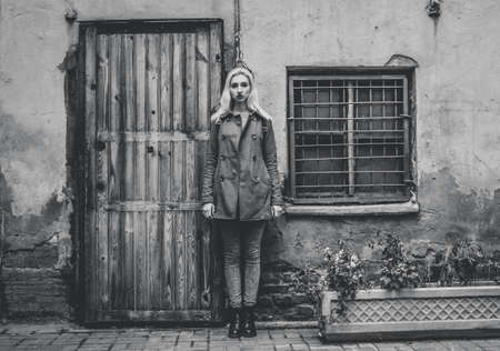 dried flowers: The girl with blue hair in the coat standing at the wall. dried flowers. Stock Photo