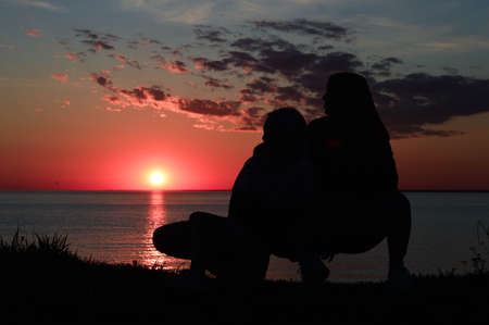 silhouettes of two girls on the shore by the sea. two girls are sitting next to