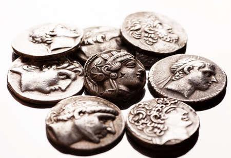 numismatics: Pile of ancient greek coins on reflective surface, closeup macro shot, selective focus Stock Photo