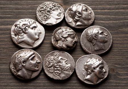greek coins: Ancient greek coins on a wooden table, selective focus Stock Photo