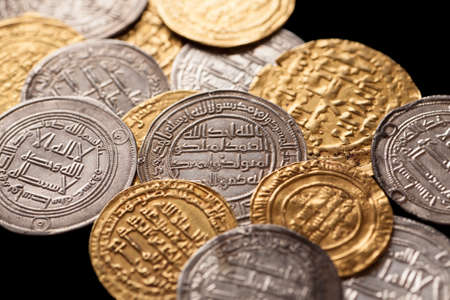 arabische letters: Heap of ancient islamic golden and silver coins with arabic letters isolated on black, closeup, selective focus