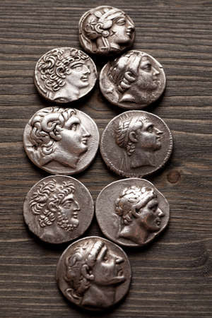 greek coins: Greek ancient silver coins on a wooden table, closeup macro shot, selective focus, vertical
