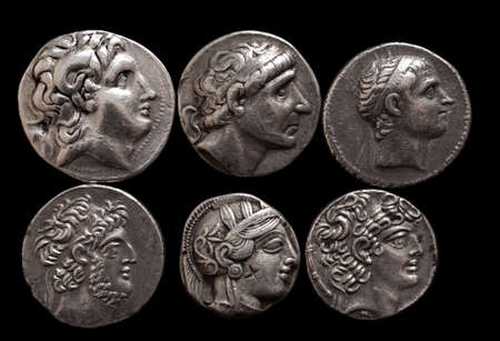 Ancient greek silver coins with portraits of rulers and gods, selective focus, closeup macro shot