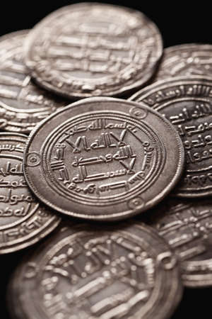 arabische letters: Oude zilveren islamitische munten met Arabische letters, selectieve aandacht, verticaal, close-up Stockfoto