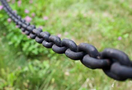 Black metal chain over green grass, selective focus, closeup shot