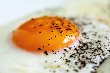 Fried egg with black pepper, macro shot