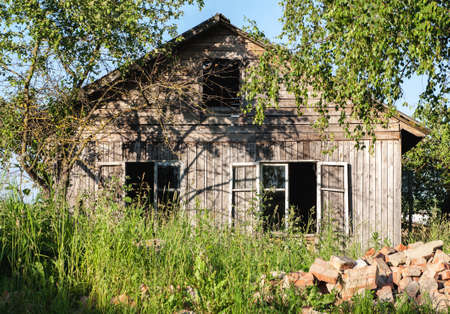 Old abandoned wooden house among green trees