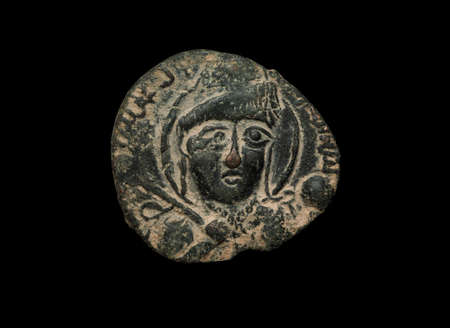 Ancient copper islamic coin with face on it isolated on black, close-up shot
