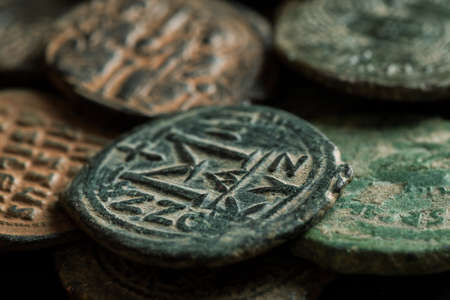 Ancient copper coins with letters and portraits of emperors, closeup