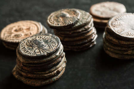 Stacks of ancient copper coins on black background, angle shot, close-up Stock Photo