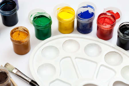 Open gouache jars with empty white plastic palette and few paintbrushes on a white background. Stock Photo