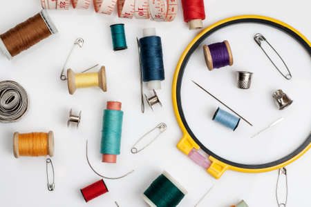 Spools of thread, needles and other sewing stuff on a white background, flat lay composition, close-up.