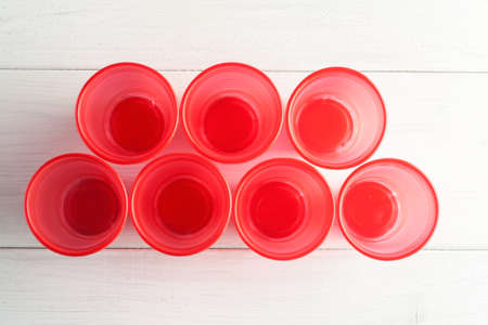Red plastic cups on a white wooden table, top view. Stock Photo