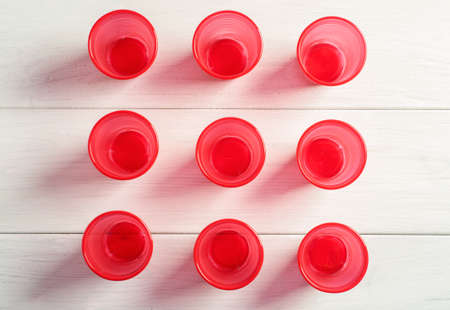 Three rows of red plastic cups on a white wooden table, top view.