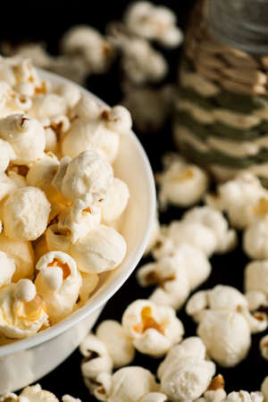 Popcorn in white ceramic bowl with salt shaker on a black wooden table, vertical. Stock Photo