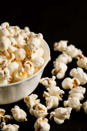 Popcorn in a white ceramic bowl on a black wooden table, selective focus, vertical.