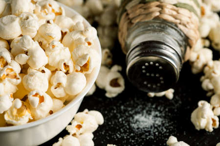 Salt shaker and popcorn in white bowl on a black wooden table. Stock Photo