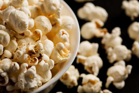 Popcorn in a white ceramic bowl on a black wooden table, selective focus. Stock Photo