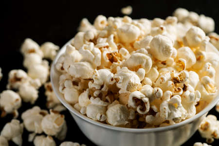 Popcorn in a white ceramic bowl on a black wooden table. Stock Photo