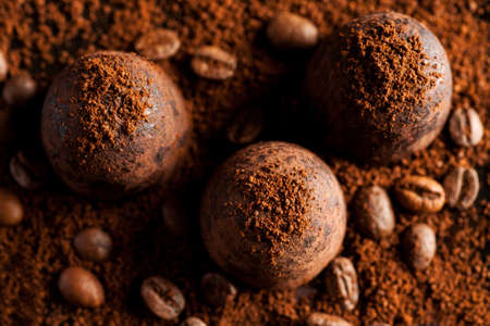 Closeup shot of three chocolate sweets with ground coffee, top view.